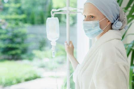 Giovane donna con gocciolamento in piedi dalla finestra dell'ospedale