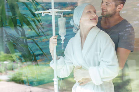 Young couple hugging and standing by the hospital window
