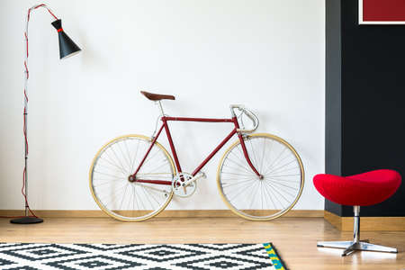 Red and stylish cycling hipster bike in apartment