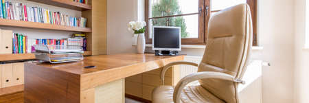 Leather chair and wooden desk in luxury office
