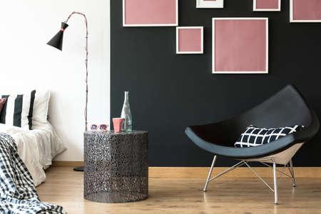 Zwarte stoel in de vorm van een driehoek met roze posters erboven.
