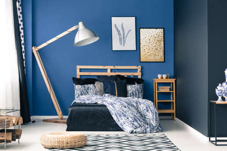bedhead: Inspiring cyan bedroom with wooden stylish lamp Stock Photo