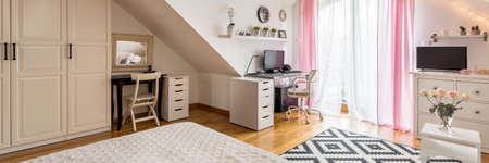Bright attic bedroom with a wardrobe and a place to work