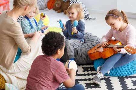 Groep kleine kinderen die muziek spelen in de kleuterschool
