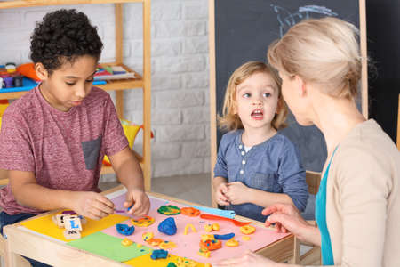 Boy and girl having fun with kindergarten teacher during classes Stock Photo