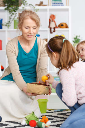 Young teacher picking up the toys after play Stock Photo
