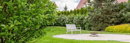 白いベンチと小さなテーブルと手入れの行き届いた家庭菜園のパノラマ