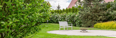 Panorama of well-kept home garden with a white bench and a small table Stok Fotoğraf