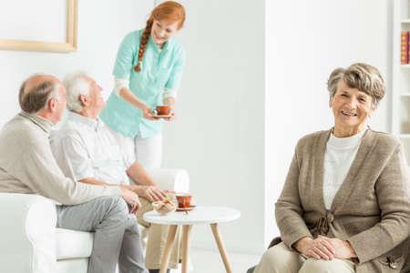 Elder lady sitting and smiling at seniors house Reklamní fotografie