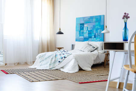 Bedroom with colorful artwork in shades of blue