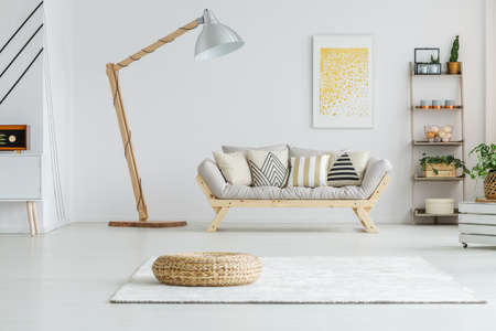 Wicker footrest standing on a white carpet in living room Foto de archivo