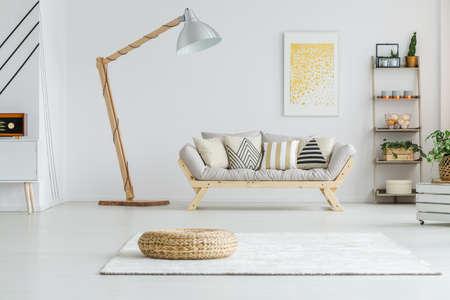 Rieten voetsteun die zich op een wit tapijt in woonkamer bevindt