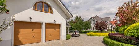 手入れの行き届いた庭園を持つ大規模な戸建住宅の二重ガレージ私道のビュー