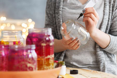 Young woman decorating DIY jars with paint