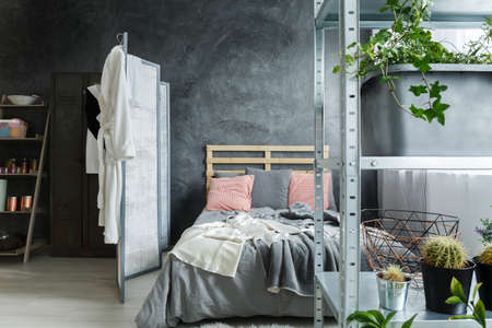 Cozy contemporary bedroom in fancy industrial loft Stok Fotoğraf