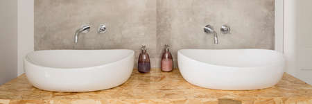 Simple and austere bathroom with two separate sinks standing on the beaverboard