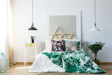 Bedclothes with botanic print in stylish, artistic bedroom