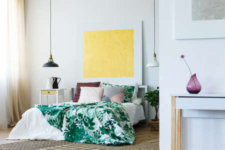 Trendy bedroom with abstract, yellow painting on the wall Stock Photo - 82253952