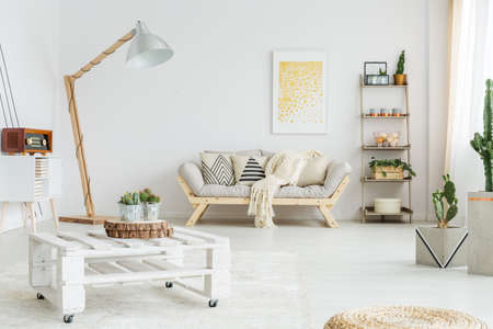 White hand-made pallet table with plants in living room Foto de archivo
