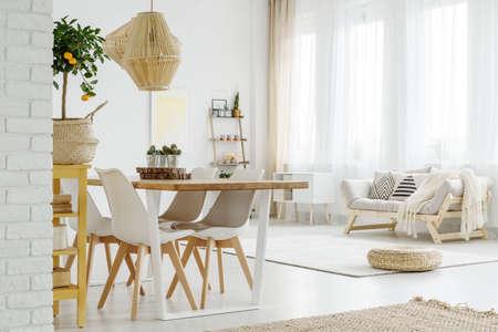 大きな窓の下に立つ枕と明るい木製ソファ