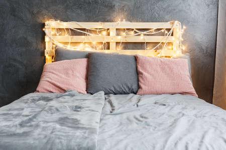 Acconciato letto sognante con testiera decorata in pallet DIY Archivio Fotografico - 82180261
