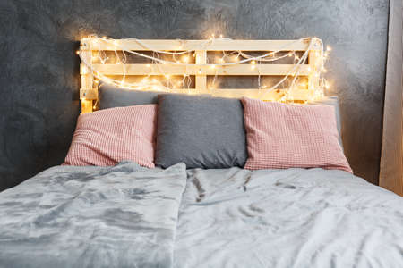 Cozy dreamy bed with decorated DIY pallet headboard Stok Fotoğraf