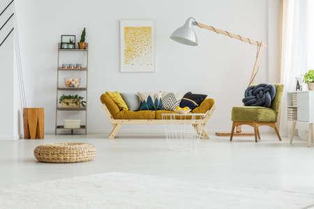 Mosterd bankje met kleurrijke kussens staan onder oversize lamp