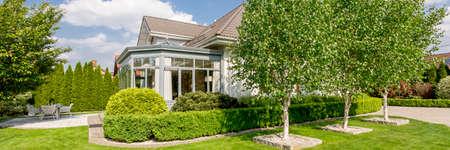 テラスや木々 と手入れの行き届いた緑の庭でエレガントなオランジェリーの家外観