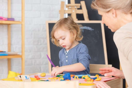 Little cute girl preparing food from plasticine in kindergarten