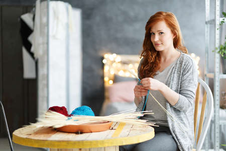 home decorating: Smiling young woman making creative decorations at stylish modern home Stock Photo