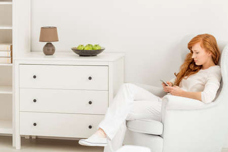 common room: Young attractive woman with smartphone sitting in big white chair