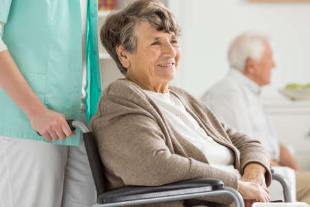 common room: Happy senior woman in wheelchair smiling during free time