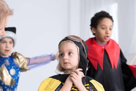 Worried little girl dressed up as a bee in kindergarten