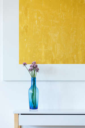 Minimal, yellow, abstract artwork and blue glass flowerpot Stock Photo