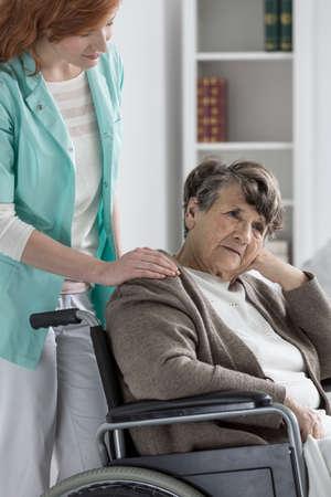 Droevige oude gehandicapte dame in rolstoel erger Stockfoto