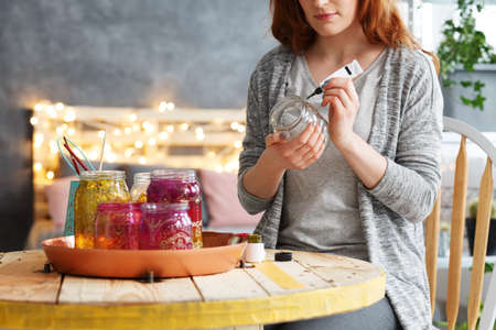 Young beautiful woman painting decorative jar at stylish home Stock Photo