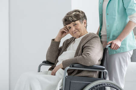 Worried senior lady sitting with blanket in wheelchair