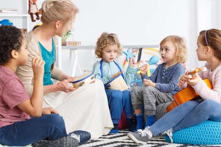 Kleine kinderen in de kleuterschool spelen instrumenten tijdens de muziekles