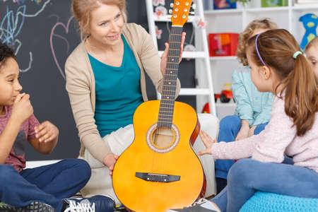Kindergarten teacher during music classes with guitar for kids