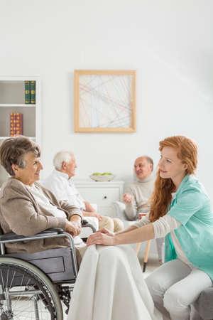 Jonge verpleegkundige die senior dame in rolstoel met een deken bedekt