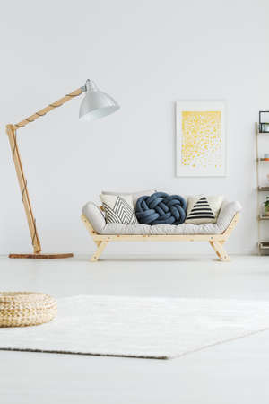 Bright wooden couch with patterned pillows and knotted cushion 스톡 콘텐츠