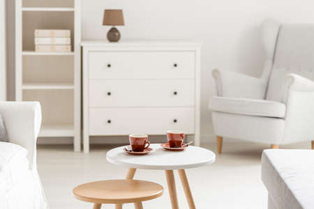 Red tea cups on small table in white room