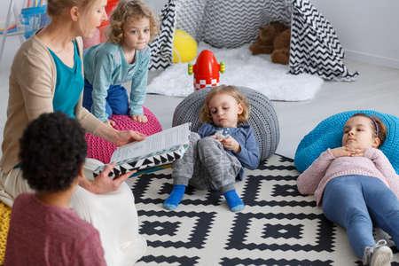 Professeur, lecture, livre, enfants, couché, tapis Banque d'images - 82253651