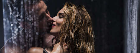 Panoramic shot of a married couple kissing passionately under the shower during foreplay photo
