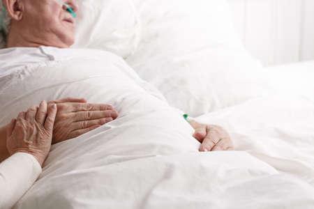Sick senior man laying in hospital bed Stock fotó
