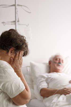 年配の女性が彼女の病気の夫の病院のベッドの横に泣いています。