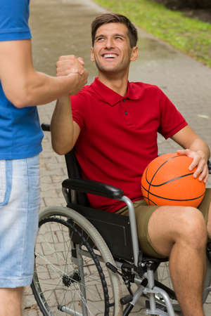 Happy disabled man holding a basketball, spending time in the park with his friend