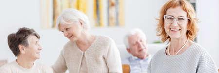 Elder lady in glasses smiling during seniors meeting Zdjęcie Seryjne