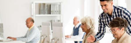 Young IT teacher explaining internet to happy elderly woman