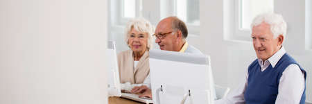 Happy elderly students working on computers during senior technology classes